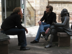 Two men and a statue discuss participation in visual anthropology