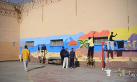 Prisoners painting a mural on their prison walls, 2012