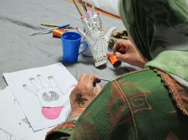 Working in henna during a painting workshop for women